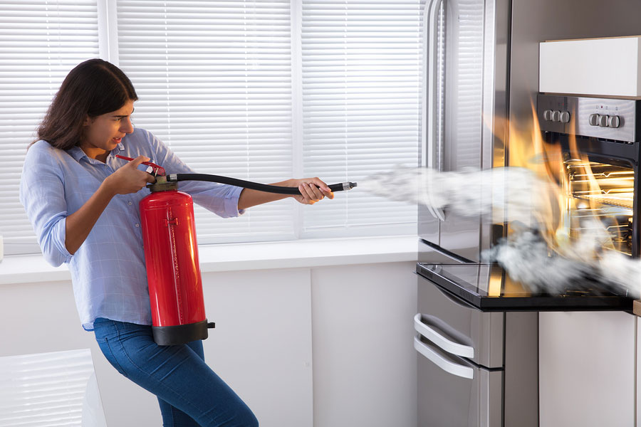 Woman putting out kitchen fire