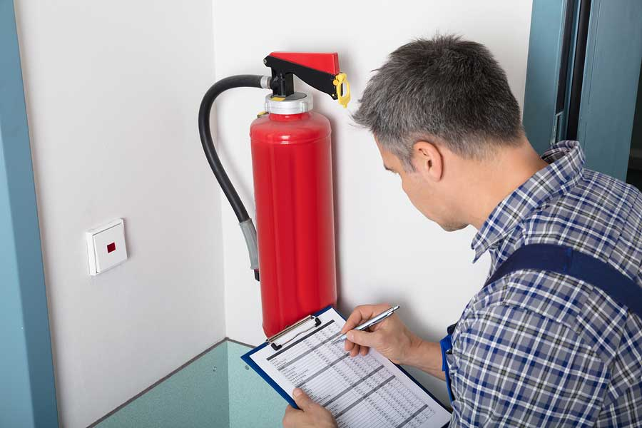 Man checking fire extinguisher