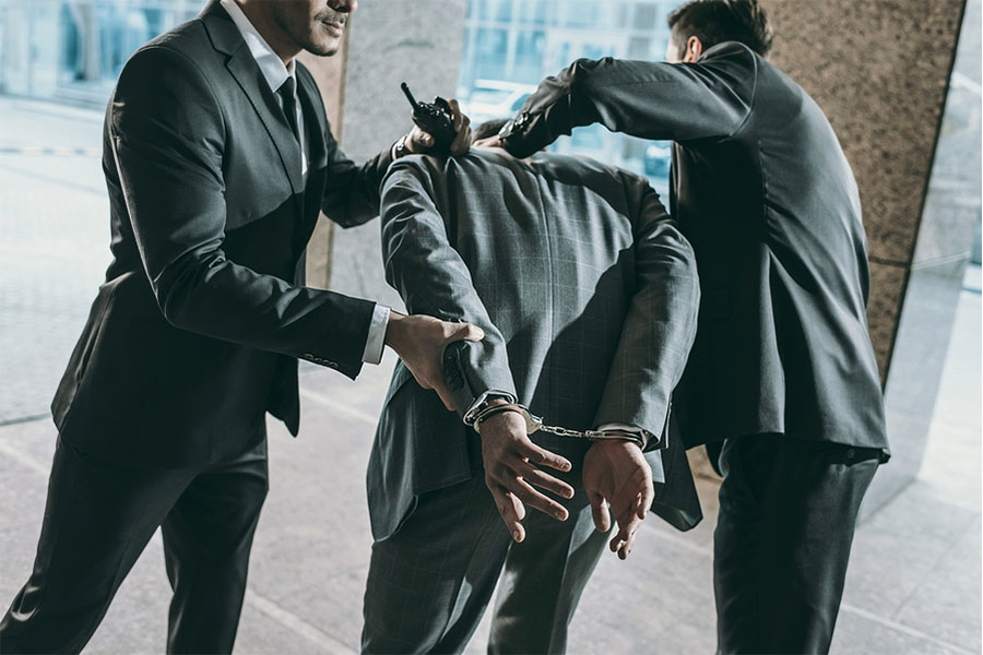 Two men handcuffing a man